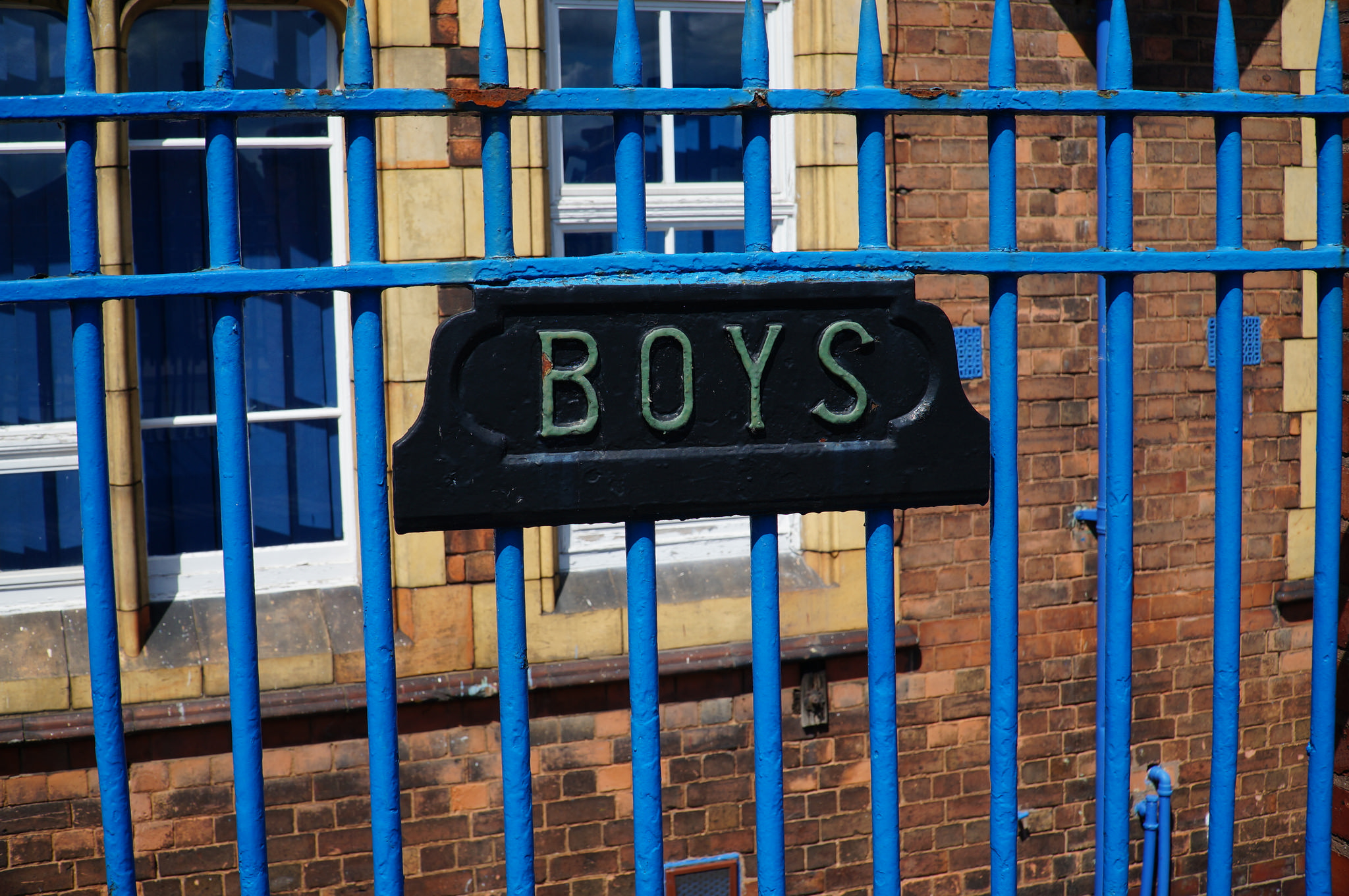 The sign says 'Boys' on railings at Benson Community School: image by Tim Ellis, CC By-NC 2.0